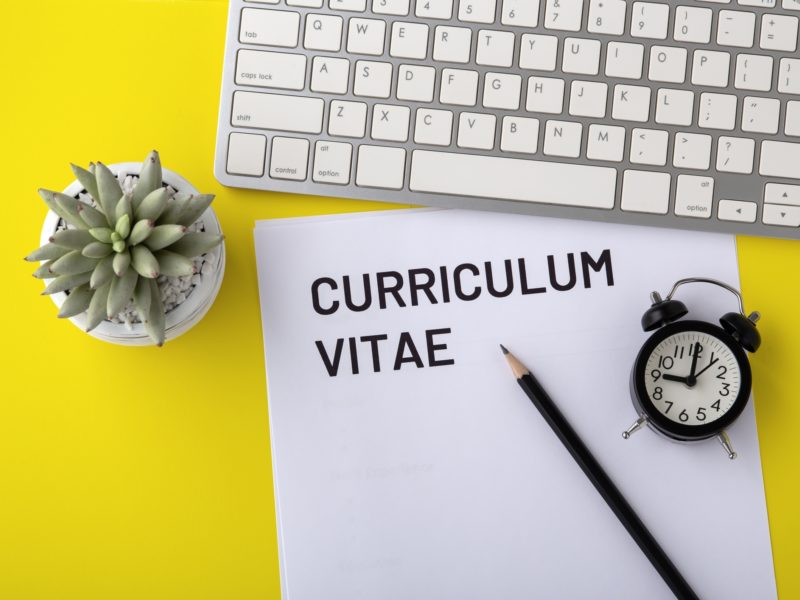 CV with keyboard and clock on yellow background 1200092879 2125x1416